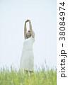 草原で伸びをする女性 38084974