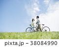 草原で自転車を押すカップル 38084990