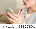 コンパクトを持ち口紅を塗る若い女性 38127801