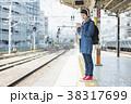 ホームで音楽を聴きながら電車を待つ女性 38317699