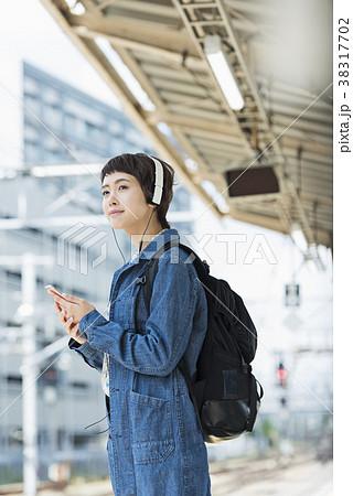 ホームで音楽を聴きながら電車を待つ女性 38317702