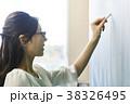 黒板にチョークで書く若い女性 38326495