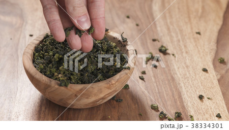 man hand check dried tea leaves in bowl on table 38334301