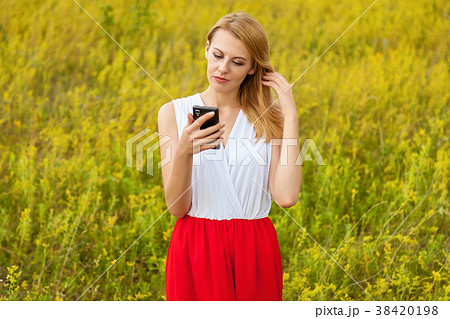 Girl in the field with phone. 38420198