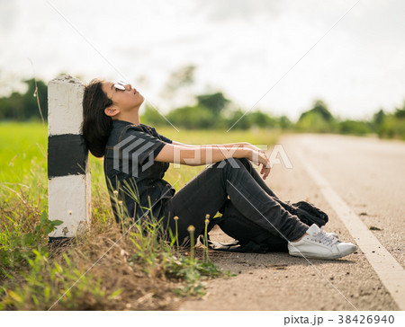 Woman sit with backpack hitchhiking along a road in countryside 38426940