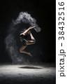 Woman in sportswear jumping in dust cloud view 38432516
