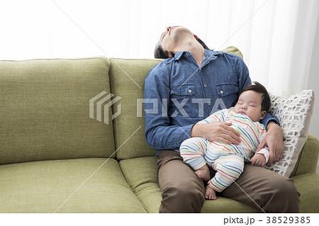 赤ちゃんを抱いて寝落ちするパパ 38529385