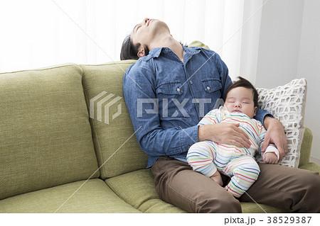 赤ちゃんを抱いて寝落ちするパパ 38529387
