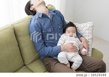 赤ちゃんを抱いて寝落ちするパパ 38529389