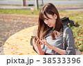 携帯をいじる若い女性 38533396