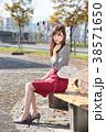 公園のベンチに座る若い女性のポートレート 38571650