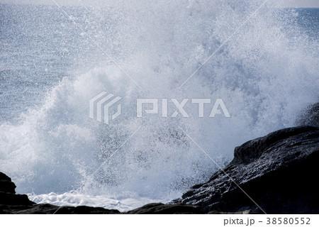 岩に打ち寄せる荒波 波しぶきイメージ 38580552