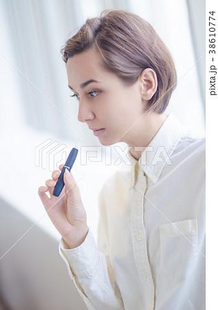 加熱式タバコを吸う女性 38610774