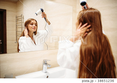 Woman drying hair with dryer in bathroom 38651236