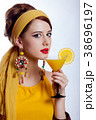 girl in 70s clothes style with tropical cocktail 38696197