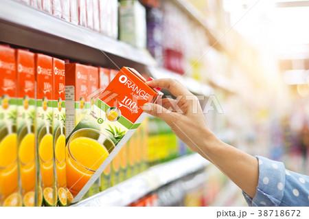Woman hand buy orange juice on shelves supermarket 38718672