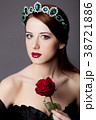 Young redhead girl with tiara and rose 38721886