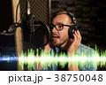 man with headphones singing at recording studio 38750048