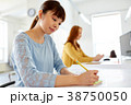 asian woman writing on sticky note at office 38750050