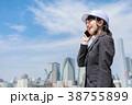 ヘルメットを着用したスーツ姿の若い女性 電話中 38755899