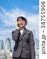 ヘルメットを着用したスーツ姿の若い女性 電話中 38755906