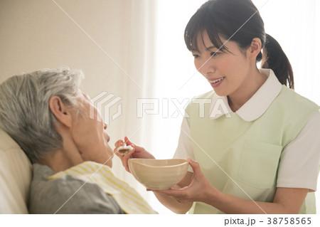 食事介助 シニア女性と介護福祉士 38758565