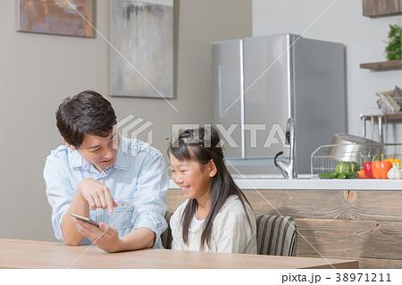 スマホを見る親子 父親 お父さん 娘 女の子 生活感 38971211