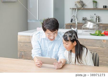 タブレット端末を操作する親子 父と娘 タブレットを見る親子 父親 お父さん 娘 女の子 生活感 38971273