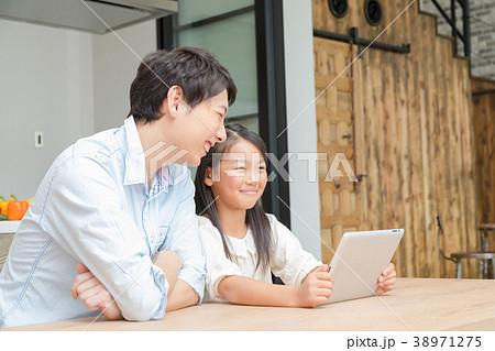 タブレット端末を操作する親子 父と娘 タブレットを見る親子 父親 お父さん 娘 女の子 生活感 38971275