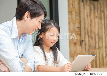 タブレット端末を操作する親子 父と娘 タブレットを見る親子 父親 お父さん 娘 女の子 生活感 38971276