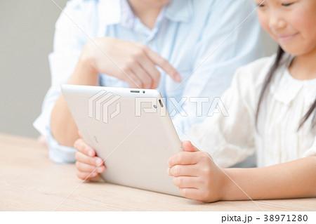 タブレット端末を操作する親子 父と娘 タブレットを見る親子 父親 お父さん 娘 女の子 生活感 38971280