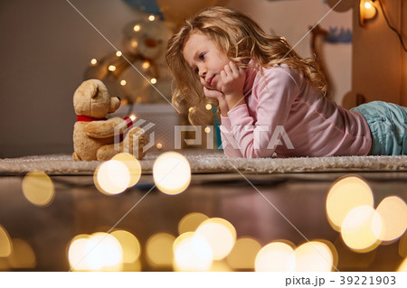 Peaceful girl on carpet with toy bear 39221903