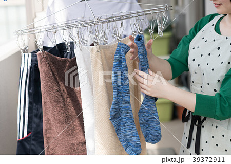 ベランダで洗濯物を干す若い女性 39372911