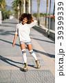 Black woman on roller skates rollerblading in beach promenade wi 39399339