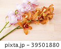 木のテーブルの上の赤茶色とピンクのデンドロビウムの花 39501880