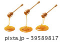 Set of wooden dippers dripping honey isolated  39589817