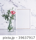 Blank frame and pink flowers over marble table 39637917