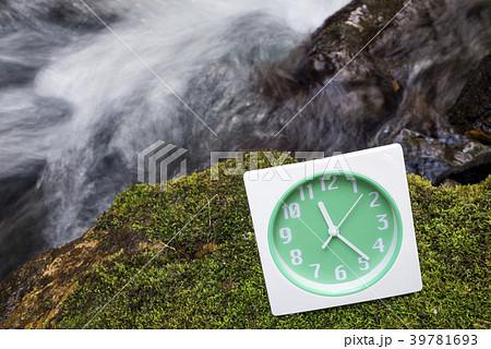 沢をバックに苔の上の置き時計 39781693