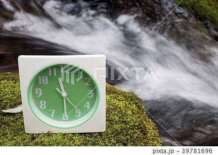 沢をバックに苔の上の置き時計 39781696