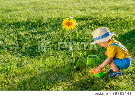 One year old baby boy using watering can  39785441