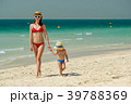 Toddler boy walking on beach with mother 39788369
