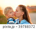 Woman and child outdoors at sunset. Mother kissing her son. 39788372