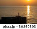 夕焼けの海岸と釣り人 39860393