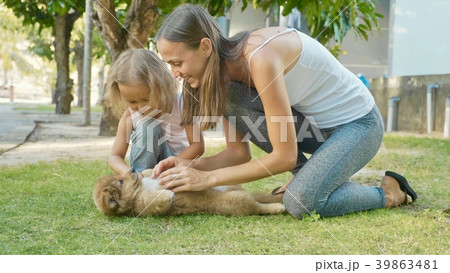Mother and child playing with puppy on a warm 39863481