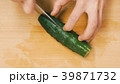Close-up of hands of chef slicing a cucumber with 39871732