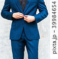 A man wearing a suit in front of a wall. 39984654