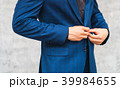Man wear suit fixing button in front of the wall 39984655