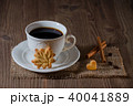a cup of coffee and cookies like leaf and heart with cinnamon, coffee beans on wooden table 40041889