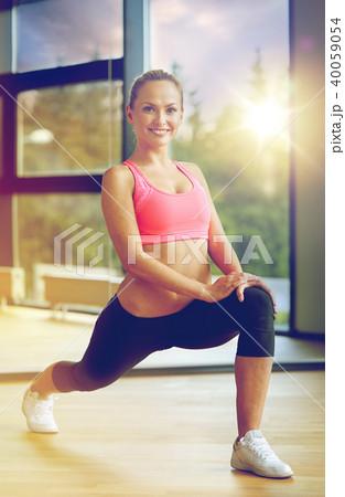 bdc5199eb2f9e smiling woman stretching leg in gymの写真素材 [40059054] - PIXTA