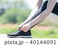 スニーカーの靴紐を結ぶ女性の足下 40144091